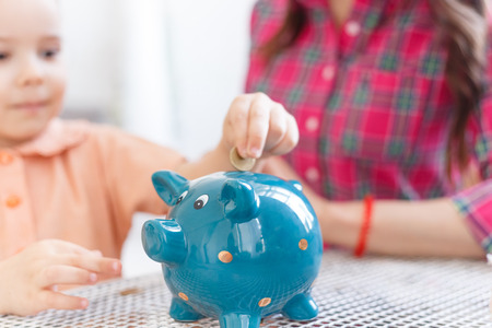 Mom teaches a little daughter to collect money in a piggy bank.