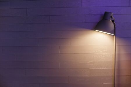 Modern lamp in a blue wall. Dark noizy photo