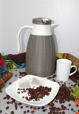 Foto de Hot beverages - a thermo flask with a mug, plate, tea bags and coffee beans - Imagen libre de derechos