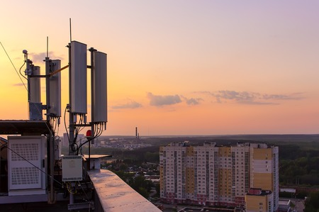 Photo pour cellular communications tower on a background of the city and beautiful sunset in summer - image libre de droit