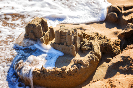 Photo for waves wash away sand castles on the beach the sea - Royalty Free Image