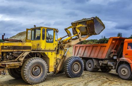 Foto de Loader excavator loads the ground in truck at the road construction - Imagen libre de derechos