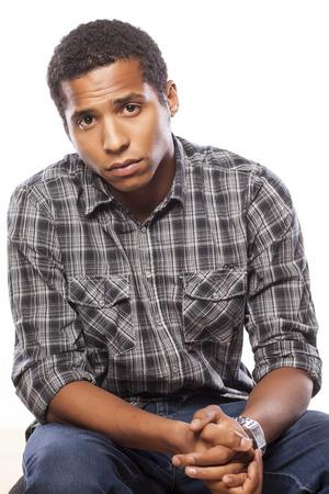 Foto de dark-skinned young man posing with a sad expression on white background - Imagen libre de derechos
