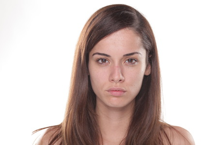 Serious young beautiful woman without make up posing on white