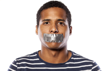 Photo pour dark-skinned young man with adhesive tape over his mouth - image libre de droit