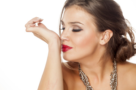 Foto de beautiful young woman enjoying the smell of the perfume on her wrist - Imagen libre de derechos