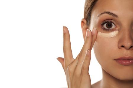 Photo pour young beautiful woman applied concealer under the eyes - image libre de droit