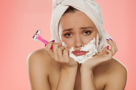Foto de disappointed young woman with foam on the face and a razor in her hand - Imagen libre de derechos