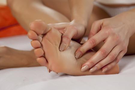 Foto de young woman massaging her tired feet - Imagen libre de derechos