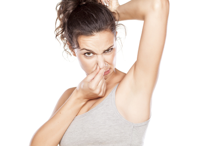 Foto de attractive girl is disgusted by her sweaty armpits - Imagen libre de derechos