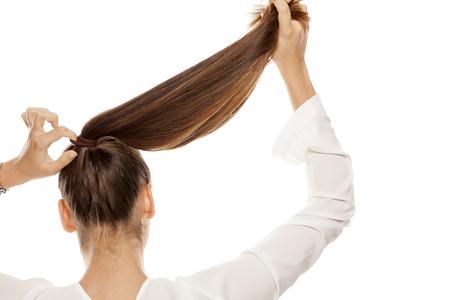 Foto de Back view of women that tightens the hair in a ponytail - Imagen libre de derechos