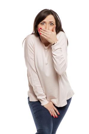 Foto de ashamed young woman need a toilet on white background - Imagen libre de derechos