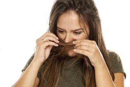 Photo pour Nervous young woman smelling her hair on white background - image libre de droit