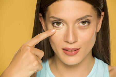 Foto de Young woman touching her low eyelids on yellow background - Imagen libre de derechos