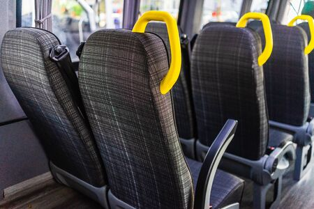 Foto per Empty seats with yellow handles in a minibus or van. - Immagine Royalty Free
