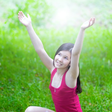 beauty girl with open hands over green grass in sunny day