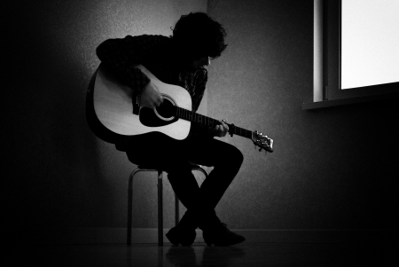 Photo for Man sitting on stool in dark room playing guitar - Royalty Free Image