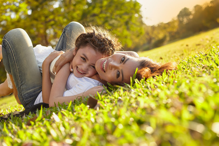 Foto de Lifestyle portrait mom and daughter in happines at the outside in the meadow - Imagen libre de derechos