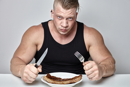 Foto de Close up big body bodybuilder eat big beef steak behind table opposite gray wall - Imagen libre de derechos