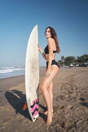 Photo for Female model with long hear style and beach wear with surfboard at sunny morning at the Balinese ocean beach - Royalty Free Image