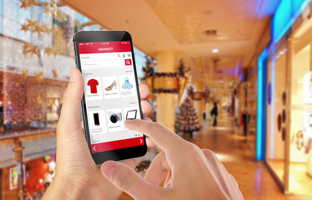 Photo pour Smart phone online shopping in man hand during Christmas. Shopping center in background. Buy clothes shoes accessories with e commerce web site - image libre de droit