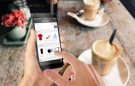Photo pour Smart phone online shopping in man hand. Shopping center in background. Buy clothes shoes accessories with e commerce web site - image libre de droit