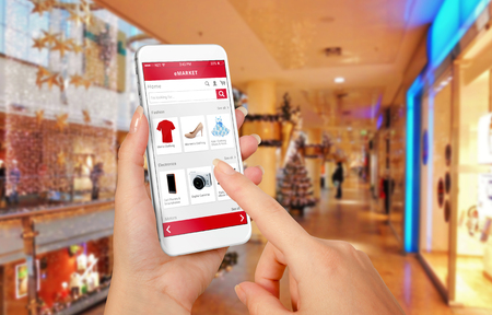Foto de Smart phone online shopping in woman hand during Christmas. Shopping center in background. Buy clothes shoes accessories with e commerce web site - Imagen libre de derechos