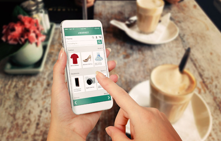 Photo pour Smart phone online shopping in woman hand. Desk with caffe in background. Buy clothes shoes accessories with e commerce web site - image libre de droit