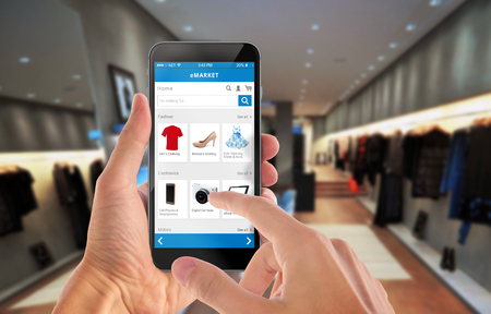 Foto de Smart phone online shopping in man hand. Shopping center in background. Buy clothes shoes accessories with e commerce web site - Imagen libre de derechos