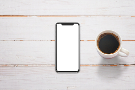 Photo pour Mobile phone with x screen on white wooden table. Cup of coffee beside. Top view. - image libre de droit