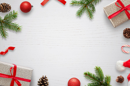 Photo for White table with Christmas decorations and space in the middle for text. Christmas composition with gifts, fir branches, lollipop, Santa hat and pinecones. Top view. - Royalty Free Image