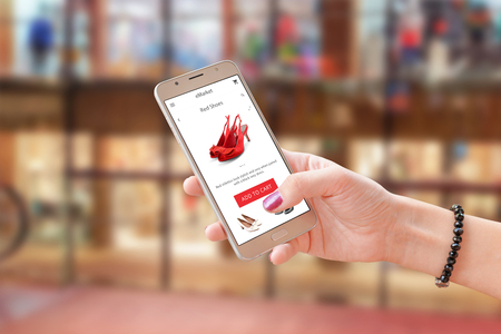 Photo pour Online shoping with commerce app or web site. Woman holding modern smart phone. Shopping center in background. - image libre de droit