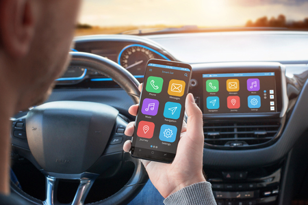 Foto de Driver uses a mobile phone with smart driving assistance apps. The app is connected to a car computer and is displayed on the board display. - Imagen libre de derechos