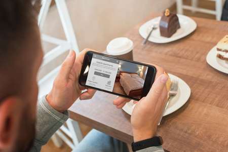 Photo for Property agent use agency web site with mobile phone to find apartment. Coffee shop in background. - Royalty Free Image