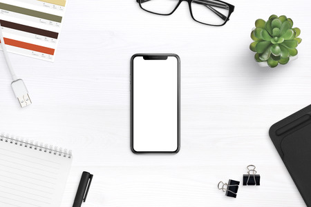Foto de Modern smartphone mockup on a desk surrounded by supplies. Isolated round screen for app or web site promotion mockup. - Imagen libre de derechos