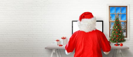 Foto de Santa work on a computer in his room. White brick wall in background with a free text space. - Imagen libre de derechos