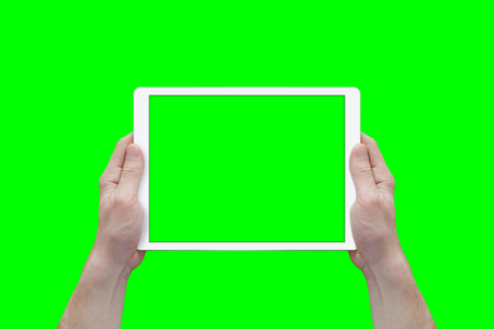 Foto de Hands hold white tablet in a horizontal position. View from first person. Isolated screen and background in green. - Imagen libre de derechos