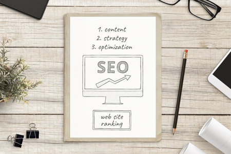 Photo pour Search engine optimization sketch on white paper surrounded with office supplies. SEO web site concept. - image libre de droit