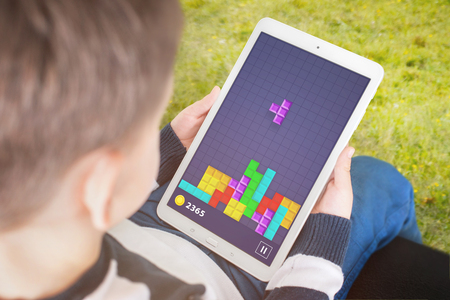 Photo pour Child play popular gane on his tablet. Concept of developing children intelligence using computer games. - image libre de droit