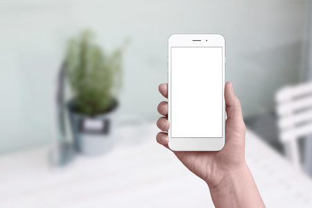 Foto de Simple white phone mockup in woman hand. Flat background with table and plant. Isolated screen for add app user interface design. - Imagen libre de derechos