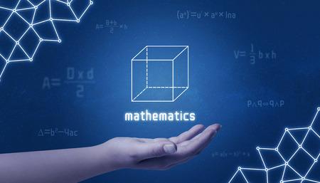 Foto de Concept of mathematics. Cube in hand surrounded by mathematical formulas and an computer network concept. - Imagen libre de derechos