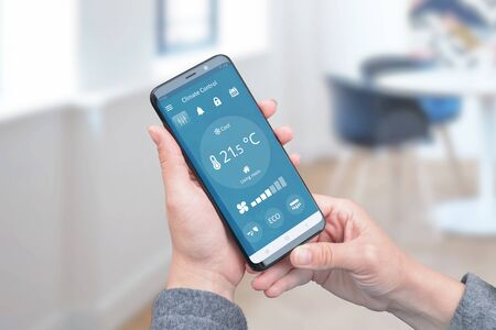 Foto de Heat control in the house with simple app on phone for remote control of air conditioners. The concept of energy efficiency, savings and ecology. - Imagen libre de derechos