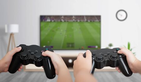 Foto de Boys play soccer on the gaming console on a large TV in the room. The concept of fun and gaming for friends. - Imagen libre de derechos