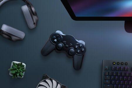 Foto de Joypad on desk surrounded with headphones, cooler, keyboard and computer display. PC gaming concept. Top view, flat lay. - Imagen libre de derechos