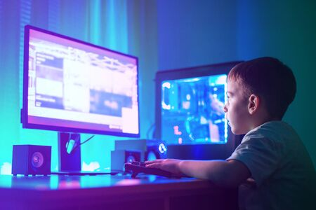 Foto de Boy play game on gaming computer or hacking a website concept. Dark scene with lots of RGB lighting. - Imagen libre de derechos
