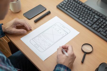 Photo pour The designer sketches, draws the layout of a mobile phone app on a wireframe. - image libre de droit