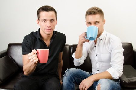 Two happy guys are drinking coffee.