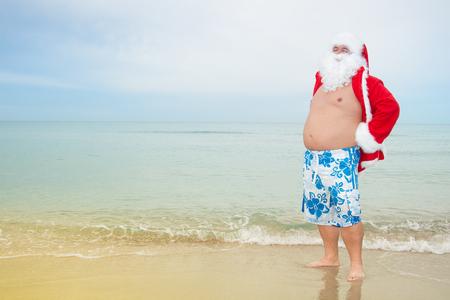 Foto de Funny Santa in shorts on the beach. - Imagen libre de derechos