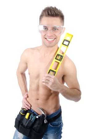 Photo for Young handsome handyman holding level. Smile and joy. Attractive young guy. Work and construction. Attractive handyman posing in the studio. White background. Isolated. - Royalty Free Image