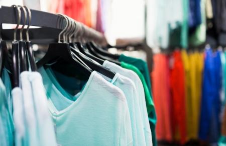 Photo pour Fashionable colorful clothes on hangers in the store - image libre de droit